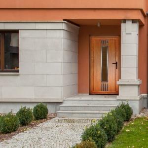 Drzwi zewnętrzne dobieramy stylistyką do otoczenia domu, elewacji budynku, a także innych elementów stolarki otworowej. Tutaj drewniane skrzydło harmonizuje z łososiowym tynkiem. Fot. Dako.