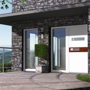 Drzwi zewnętrzne możemy dobrać również na zasadzie kontrastu z elewacją domu. Tutaj aluminiowe drzwi pomalowane na biało pięknie kontrastują z ciemnym, kamiennym wykończeniem fasady budynku. Fot. Internorm.