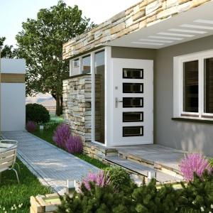Białe skrzydło drzwi zewnętrznych zdobią symetryczne przeszklenia w pionowym rzędzie, przecinające całe drzwi. Dodatkowym akcentem dekoracyjnym jest zamknięcie przeszkleń w ciemniejsze ramy. Ze stylistyką drzwi harmonizuje sąsiadujące z nimi okno. Fot. Pol-skone.
