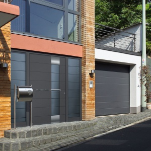 Drzwi zewnętrzne powinny harmonizować z towarzyszącymi im innymi elementami stolarki otworowej, jak np. brama garażowa. Warto postawić na produkty z oferty jednego producenta, dobierając identyczne rozwiązania wzornicze. Fot. Hoermann.