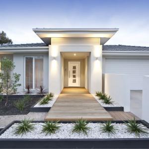 Białe drzwi zewnętrzne dopasowano kolorystycznie to barwy całego domu. Elewacje wykończono jasnoszarym tynkiem, a brama garażowa jest biała - podobnie jak drzwi. Całość prezentuje się nad wyraz elegancko i delikatnie. Fot. Dako.