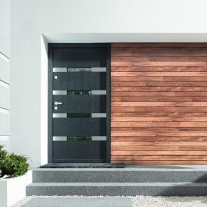 Drzwi zewnętrzne utrzymane w nowoczesnej stylistyce udekorowano poziomymi, smukłymi przeszkleniami, które ciekawie korespondują z drewnianą deską na elewacji. Ułożone w poziomie poszczególne deski zdają się być wizualnym przedłużeniem wzornictwa drzwi. Fot. Porta KMI Poland.