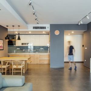 Jednorodne posadzka na podłodze oraz ściany w tym samym kolorze spajają wizualnie otwartą strefę dzienną. Projekt: Le Studio. Fot. Thien Thach.