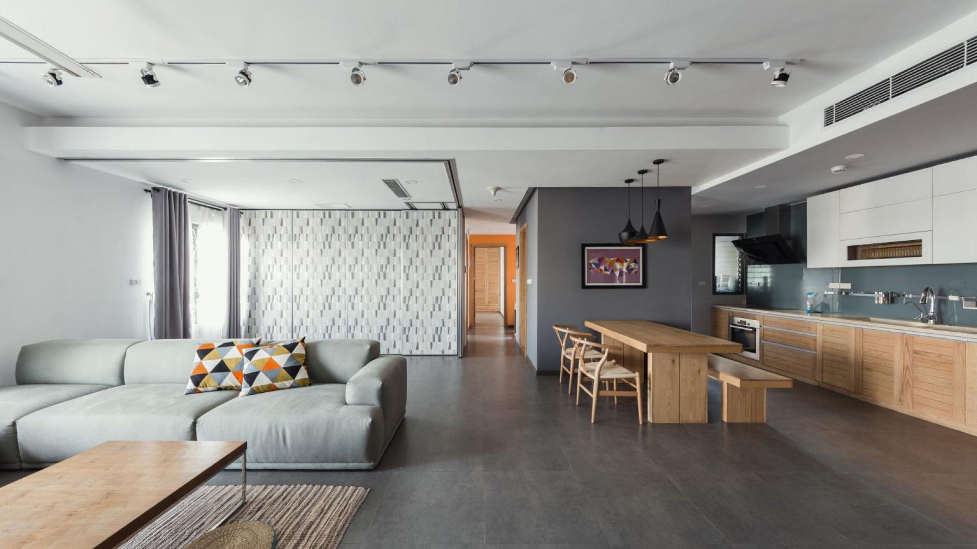 Kuchnię otwarto na salon, a granicę pomiędzy pomieszczeniami wyznacza umownie drewniany stół jadalniany. Projekt: Le Studio. Fot. Thien Thach.