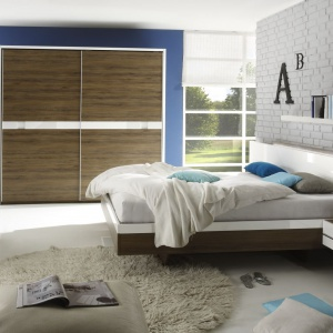 Zoe to nowoczesna kolekcja mebli do sypialni. Biel na wysoki połysk połączono tu z ciepłem drewna. Wyjątkowym elementem sypialni jest łóżko z podświetlanym panelem ściennym pełniącym rolę zagłówka. Cena zestawu: od. 3.799 zł. Fot. Helvetia Wieruszów