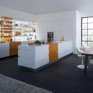 Kto powiedział, że fronty mebli kuchennych muszą być jednorodne? Tutaj białą zabudowę wykończoną w macie przecina pas w kolorze ciemnej żółci. Dodatkowym, interesującym detalem są fronty-żaluzje którymi można zasłonić szafki nad dolną zabudową. Fot. Leicht, model Tocco.