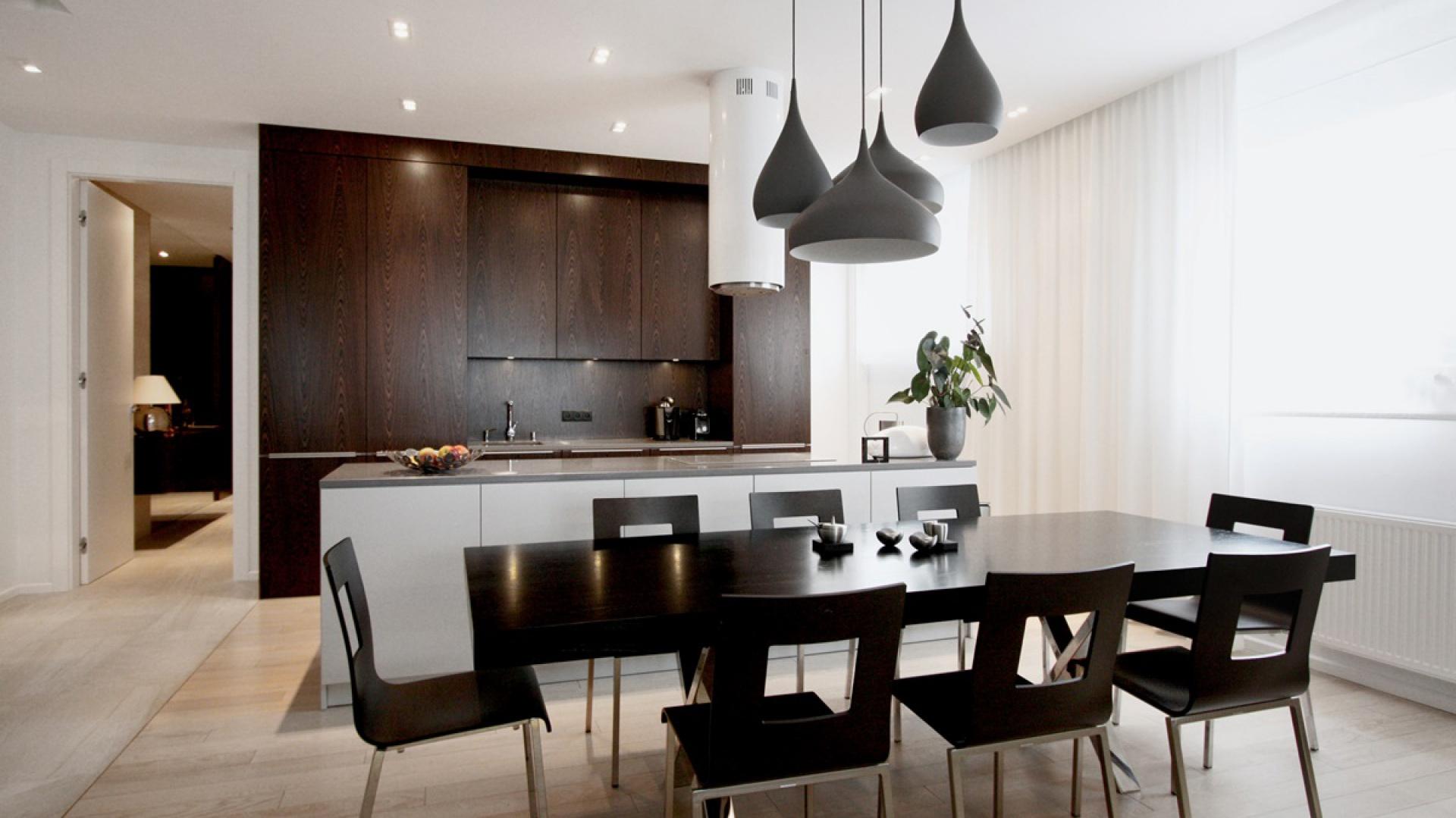 Stylowe, ciemne meble w kuchni stworzyły zgraną drużynę ze stołem i krzesłami w jadalni. Do zespołu próbują dołączyć się oryginalne lampy w kształcie spadających kropel. Projekt: Soma Architekci. Fot. Soma Architekci.