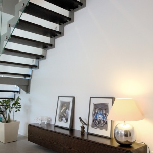 Przestrzeń pod schodami została wykorzystana do wyeksponowania pamiątek i drobiazgów właścicieli. Dobrym pomysłem jest umieszczenie wzdłuż całej wolnej długości szafki, która doskonale dopasowuje się kolorem do stopni schodów.  Projekt: Soma Architekci. Fot. Soma Architekci.
