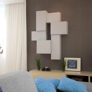 Biała szafka o nieregularnych kształtach sprawi, że wzrok gości skupi się właśnie na niej, a jednocześnie podkreśli tradycyjną szarość ścian. Projekt: Soma Architekci. Fot. Soma Architekci.