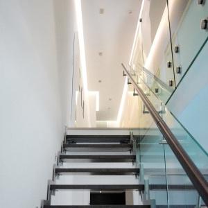 Wykorzystanie szkła w balustradzie schodów sprawi, że odbijające się w nim światło da złudzenie nieskończenie długiego korytarza, ale również będzie stanowiło dobraną parę z ciemnym kolorem schodów i drewnem poręczy. Projekt: Soma Architekci. Fot. Soma Architekci.