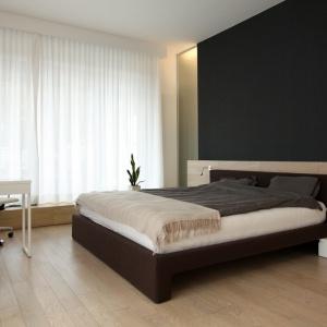 """Drewniane panele podłogi oraz ściany za wezgłowiem łóżka """"gaszą"""" czerń ściany. Białe biurko oraz obrotowy fotel w połączeniu z ciemną ramą łóżka kojarzą się kolorami czekolady. Projekt: Soma Architekci. Fot. Soma Architekci."""