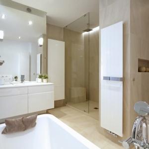 Duża powierzchnia łazienki została zaaranżowana za pomocą luster, szkła i bieli. W wyniku tego wnętrze zyskało jasność i przestronność. Ciekawym pomysłem stało się również wykorzystanie dodatkowej przestrzeni poprzez umieszczenie we wnęce przeszklonej kabiny prysznicowej. Projekt: Soma Architekci. Fot. Soma Architekci.