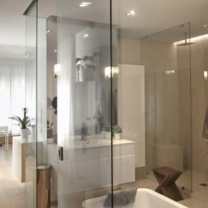Łazienka znajdująca się we wnętrzu sypialni została oddzielona od tego pomieszczenia szklanymi ścianami. To zarówno komfortowe, jak i oszczędne rozwiązanie. Projekt: Soma Architekci. Fot. Soma Architekci.