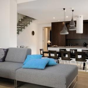 Szarość i biel otwartych pomieszczeń została ożywiona kolorowym akcentem w postaci błękitnych poduszek na kanapie. Fronty mebli kuchennych nadają otoczeniu eleganckiego sznytu. Projekt: Soma Architekci. Fot. Soma Architekci.