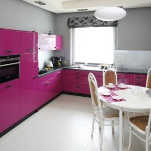 Wnętrze kuchni nie zostało odosobnione. Poprzez nowoczesne jej zaaranżowanie – wykorzystanie fioletowych frontów aneksu kuchennego, czarnych cokołów i białego stołu oraz krzeseł kuchnia jest bliską siostra salonu utrzymanych w nieco innych klimatach.