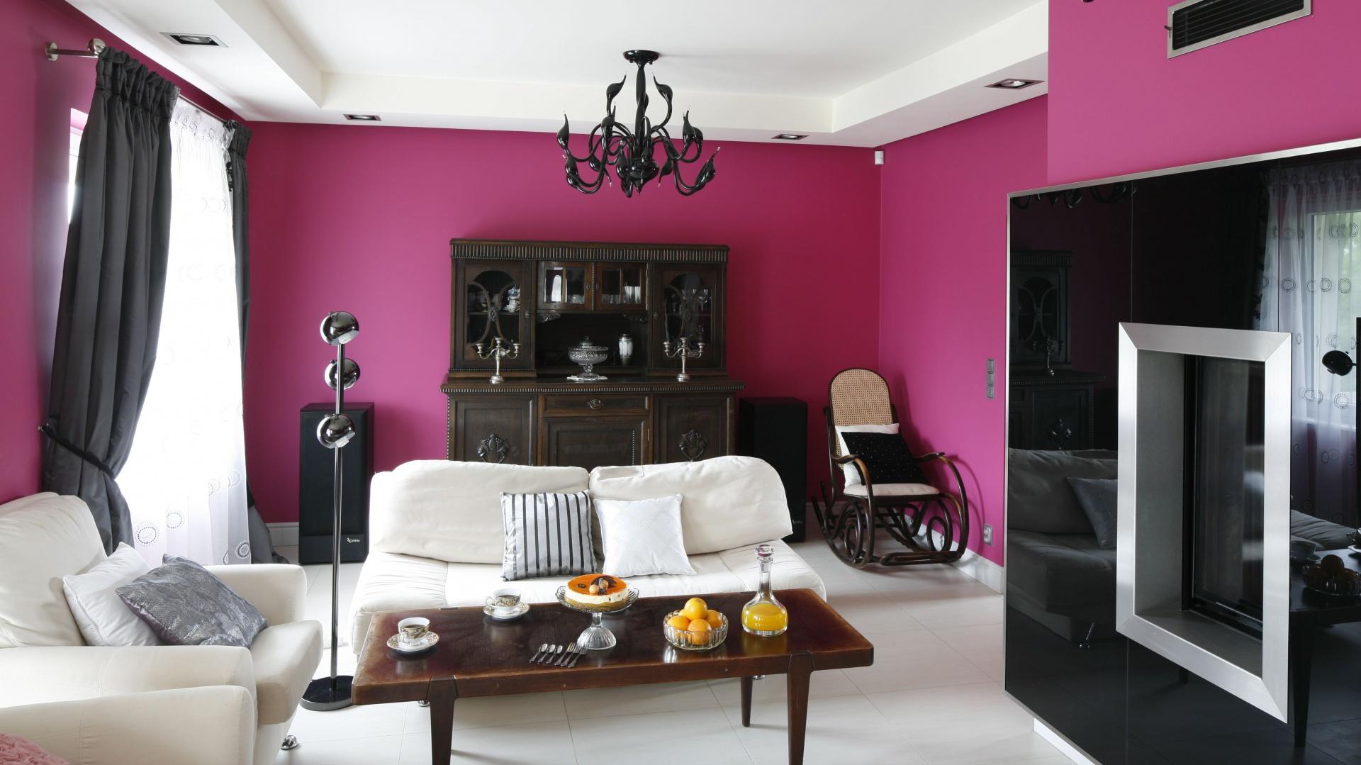 Cała przestrzeń salonu została wykorzystana do maksimum. Białe meble w połączeniu z dawnym kredensem i stolikiem tworzą idealne tło do czarnego kominka.