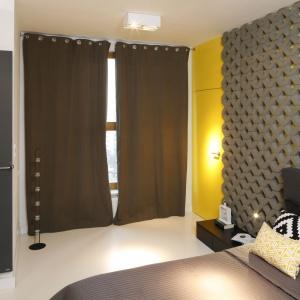 Duże okno daje dużo naturalnego światła. Jednak gdy zasłonimy je brązowymi, wysokimi zasłonami, które idealnie wkomponowują się w kolorystykę szafki nocnej, sypialnia nabierze wyjątkowego klimatu.