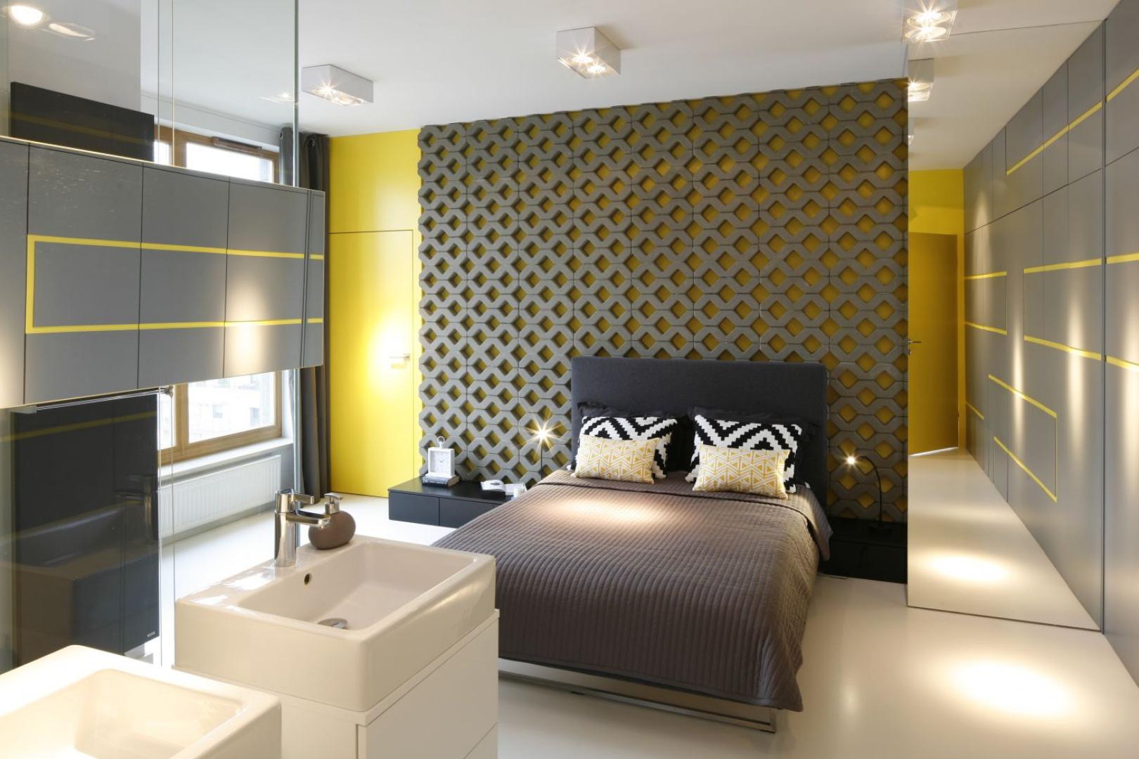 Szara niby-ściana ukrywa w sobie pojemną szafę, od której wzrok odwracają żółte zarysy figur geometrycznych oświetlanych przez niestandardowe lampy sufitowe.