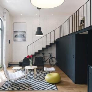 Mieszkanie w stylu loft urządzono na dwóch poziomach, otwierając parter na antresolę, z którą łączą go czarne, industrialne schody. Projekt: Eduardo Cadaval & Clara Solà-Morales. Fot. Miguel de Guzmán.