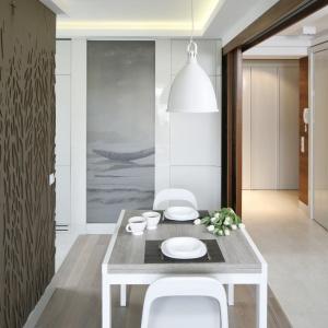 Między jadalnią a holem są szerokie przesuwne drzwi. Ich wypełnienie to szkło z fotografią nadrukowaną na transparentnej folii. Podobnie jest wykonane przeszklenie w ścianie przy wejściu do kuchni. Projekt: Małgorzata Mazur. Fot. Bartosz Jarosz.