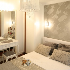 Elegancką sypialnię urządzono w bieli, beżach i szarościach. Znalazło się tu także miejsce dla stylowej toaletki, która na tle ujętego w klasyczne ramy lustra prezentuje się niezwykle efektownie. Projekt: Małgorzata Mazur. Fot. Bartosz Jarosz.
