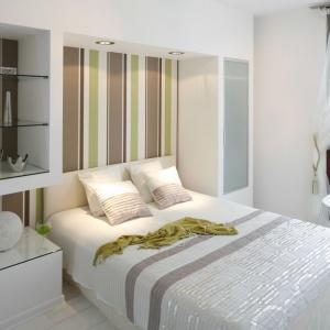 Sypialnia, podobnie jak całe mieszkanie, utrzymana jest w lekkiej, naturalnej stylistyce. Dominuje tu biel, której monochromatyczność przerywa dekoracyjna tapeta w pasy. Projekt: Jolanta Kwilman. Fot. Bartosz Jarosz.
