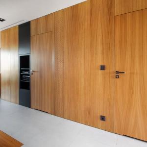 Zabudowa w ciepłym, przytulnym kolorze drewna spaja wizualnie kuchnię z korytarzem, prowadzącym do pozostałych pomieszczeń. . Projekt: mode:lina architekci. Fot. Marcin Ratajczak.