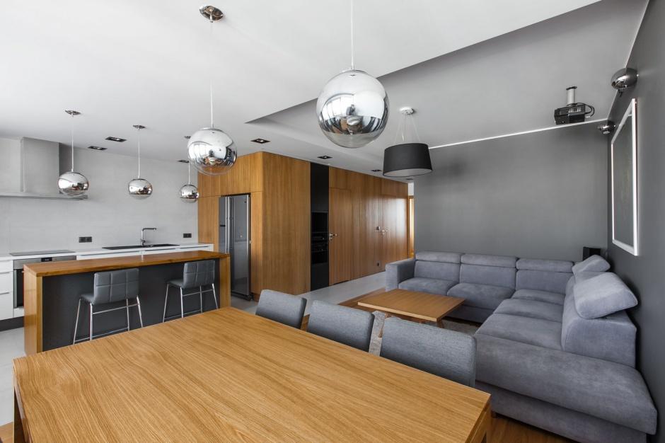 Architekci wyburzyli i wyrównali ściany, co pozwoliło im otworzyć wnętrze. W takiej strefie dziennej znalazło się miejsce na dużą kuchnię, jadalnię, salon, a nawet spiżarnię w boxie. Projekt: mode:lina architekci. Fot. Marcin Ratajczak.