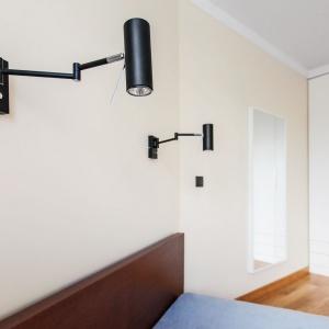 W sypialni postawiono na biel, przełamaną mocną czernią w postaci opraw lampek nocnych. Projekt: mode:lina architekci. Fot. Marcin Ratajczak.