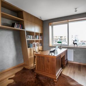 Z dużym, solidnym biurkiem w klasycznym stylu ciekawie kontrastuje nieregularna, asymetryczna biblioteczka. Projekt: mode:lina architekci. Fot. Marcin Ratajczak.