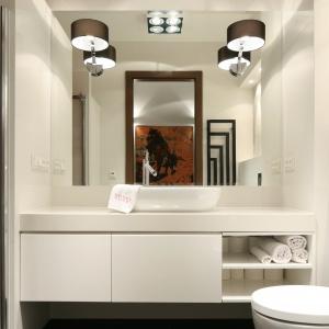 Łazienka w bieli została urządzona nowocześnie, co podkreślają proste formy zabudowy oraz stylowo, co akcentuje chociażby oświetlenie.  Proj. Małgorzata Galewska. Fot. Bartosz Jarosz.