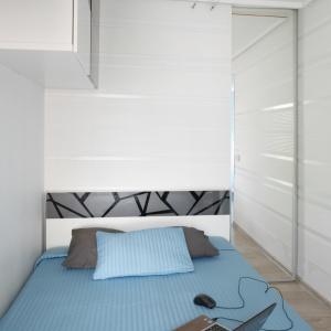 Szafki umieszczone, wysoko nad łóżkiem nie zagracą przestrzeni i zapewnią dodatkowe miejsce na przechowywanie. Projekt: Marta Kilan. Fot. Bartosz Jarosz.