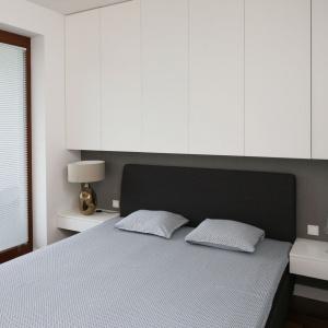 Dzięki wysokim szafkom, umieszczonym np. nad łóżkiem możemy sprawić, że mała sypialnia będzie wydawała się wyższa. Projekt: Agnieszka Ludwinowska. Fot. Bartosz Jarosz.