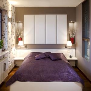 Sypialnia jest niewielka, ale urządzona bardzo funkcjonalnie. Ścianę za łóżkiem zabudowano białymi szafkami, które oferują dodatkowe miejsce do przechowywania. Projekt: Agnieszka Kubasik. Fot. Bartosz Jarosz.