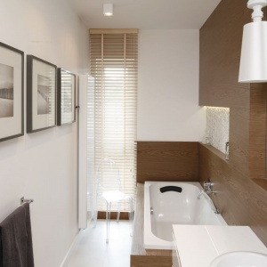 Gustowne dodatki, biała ceramika i cieplejszy niż w części dziennej odcień drewna, zmieniają łazienkę w luksusowy salon kąpielowy. Projekt: Małgorzata Galewska. Fot. Bartosz Jarosz.