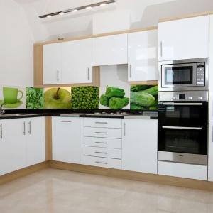 Ścianę nad blatem w tej białej kuchni zdobi kolaż zielonych smakołyków: odnajdziemy tutaj ogórek, paprykę, zielony groszek. Żywe, świeże kolory dodają wnętrzu energii. Fot. Artofwall.