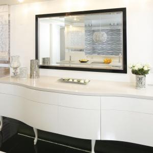 Biała kuchnia dodatkowo jest powiększona optycznie za sprawą dużego lustra, które zawisło nad elegancką komodą na nóżkach. Projekt: Katarzyna Uszok. Fot. Bartosz Jarosz.