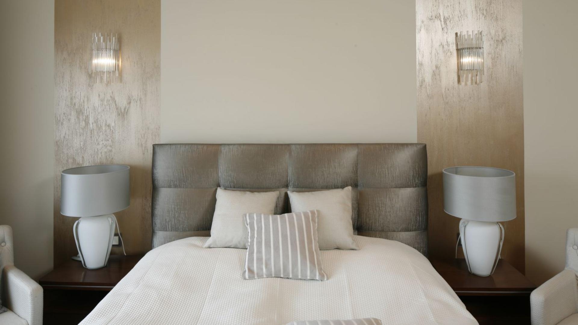 Elegancką sypialnię urządzono w stonowanych beżach i brązach. Ścianę nad łóżkiem udekorowano farbę oraz złotym stukiem. Projekt: Kinga Śliwa. Fot. Bartosz Jarosz.