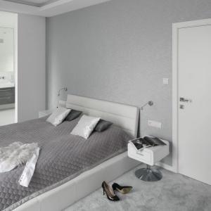 Sypialnię urządzono w modnych szarościach i bieli. Ścianę za łóżkiem zdobi jednolita tapeta w połyskującym kolorze srebra. Projekt: Katarzyna Mikulska-Sękalska. Fot. Bartosz Jarosz.