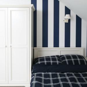 Sypialnię urządzono w marynistycznym stylu. Stąd pomalowana w biało-granatowe pasy ściana za wezgłowiem. Projekt: Katarzyna Mikulska-Sękalska. Fot. Bartosz Jarosz.
