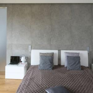 Urządzono w palecie chłodnych barw sypialnię zdominowały szarości. Ścianę za wezgłowie łóżka zdobią płyty imitujące beton. Projekt: Małgorzata Galewska. Fot. Bartosz Jarosz.
