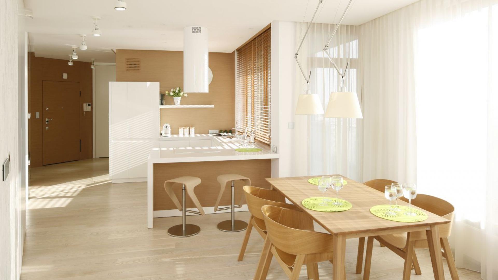 Minimalistyczna, nowoczesna kuchnia, w której panuje ciepły kolor drewna, przełamany śnieżną bielą. Projekt: Maciej Brzostek. Fot. Bartosz Jarosz.