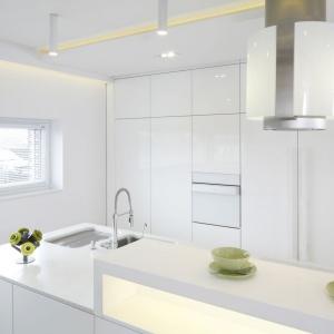 Strefa robocza kuchni jest dyskretnie osłonięta podwyższeniem w formie efektownego, podświetlonego bufetu. Projekt: Dominik Respondek. Fot. Bartosz Jarosz.