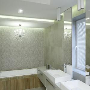 Charakterystyczne dla projektu strefy dziennej biel i szarości odnajdziemy także w łazience przy sypialni. Tutaj dodatkowo styl wnętrzu nadaje dekoracyjna tapeta, a wizualnie ocieplają drewnopodobne płytki. Projekt: Dominik Respondek. Fot. Bartosz Jarosz.