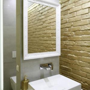 W drugiej łazience ścianę wykończono cegłą, pomalowaną na złoty kolor, nawiązując tym samym do ściany w jadalni. Projekt: Dominik Respondek. Fot. Bartosz Jarosz.