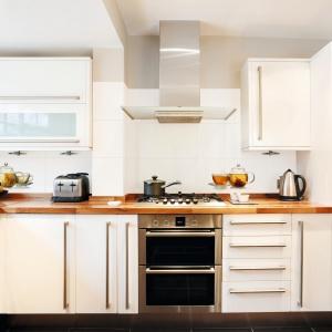 Lśniące białe płytki nad blatem optycznie powiększają kuchnię. Ozdobny dekor z dzbankiem herbaty nadaje bardziej domowy, przytulny charakter – seria Opp! marki Ceramstic. Fot. Ceramstic.
