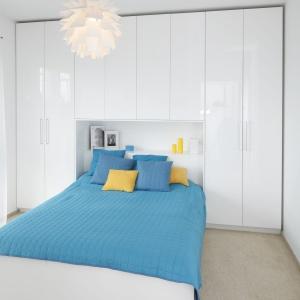 Sypialnia, podobnie jak całe wnętrze, urządzona została w bieli. W tym kolorze są zarówno meble, jak i ściany. Całość ociepla wykładzina w beżowym kolorze. Projekt: Katarzyna Uszok. Fot. Bartosz Jarosz.