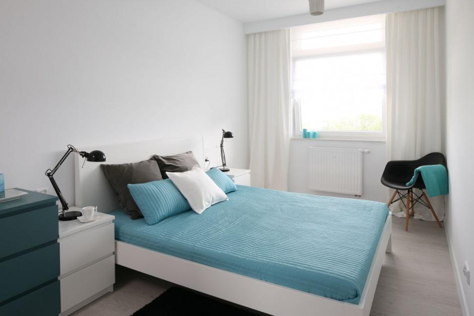 Sypialnię w bloku urządzono w czystej bieli. Do niej dobrano szare i turkusowe dodatki, które ożywiają monochromatyczną przestrzeń. Projekt: Anna Maria Sokołowska. Fot. Bartosz Jarosz.