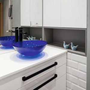 Ulubionym kolorem właścicielki mieszkania jest niebieski. Szklana umywalka w kształci misy idealnie przemyca tą barwę do wnętrza łazienki. Projekt: Ewa Para. Fot. Bartosz Jarosz.