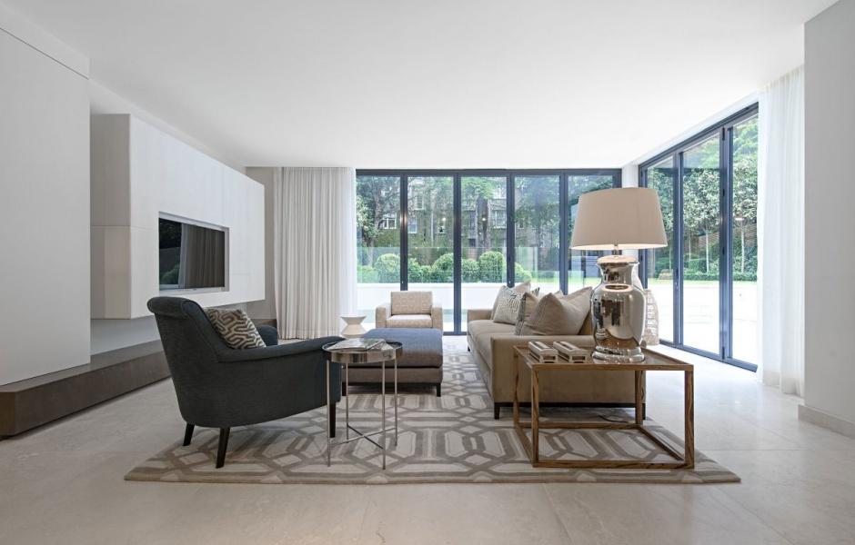 Brak dekoracji w salonie to sposób na wyeksponowanie ciekawych mebli oraz dopasowanych do nich dodatków. Chłodne odcienie ścian przełamano różnymi odcieniami beżu, ocieplono zaś drewnianym stolikiem. Projekt: Rupert Martineau, SHH Architects. Fot. Alastair Lever, Gareth Gardner.